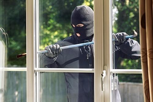 Einbrecher mit Brecheisen vor Fenster